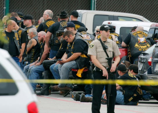 In this May 17, 2015, file photo, a McLennan County deputy stands guard near a group of bikers in the parking lot of the Twin Peaks restaurant in Waco, Texas. An attorney for six men arrested after the 2015 shootout between rival biker gangs that left nine people dead and at least 20 injured asked a district court judge Wednesday, June 5, 2019, to assign a special master to supervise the return of items seized from the nearly 200 detained bikers.