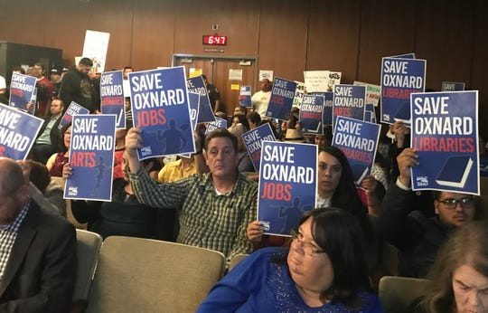 Audience members at a Tuesday council meeting hold up signs protesting the proposed budget cuts in Oxnard.