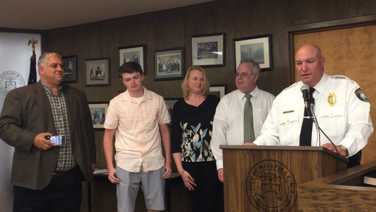 Recently retired Millville police Capt. Daniel Baer Jr. (second from right) listens to Chief Jody Farabella (podium) during a presentation at the City Commission meeting. Left to right: Commissioner Joseph Pepitone and Baer's son and wife, Daniel and Deborah.