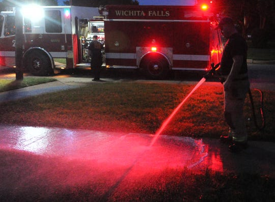 A Wichita Falls firefighter washes blood from a sidewalk located on Lincoln Street where police wrestled an alleged armed suspect, Wednesday night.