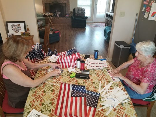 "Debbie Dobbins, left, Neighborhood by the Base Realtor, planted 500 American flags off Missile Road and Expressway Village. In honor of Memorial Day, each flag bore the tag, ""To All Our Veterans, We Will Never Forget."" Her mother, Peggy Mew, right, helped prepare the flags and drove Dobbins on her route."