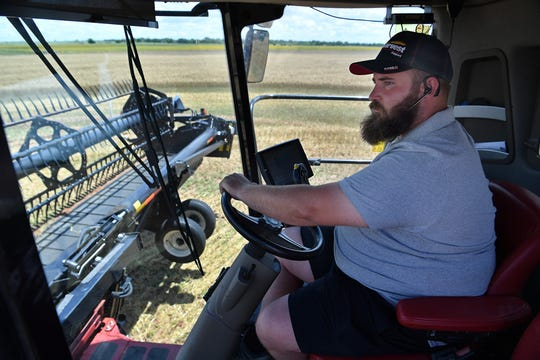 Jack Terblanche runs a combine in a wheat field east of Burkburnett Thursday. Wet fields and high moisture content in the wheat crop has delayed harvest.