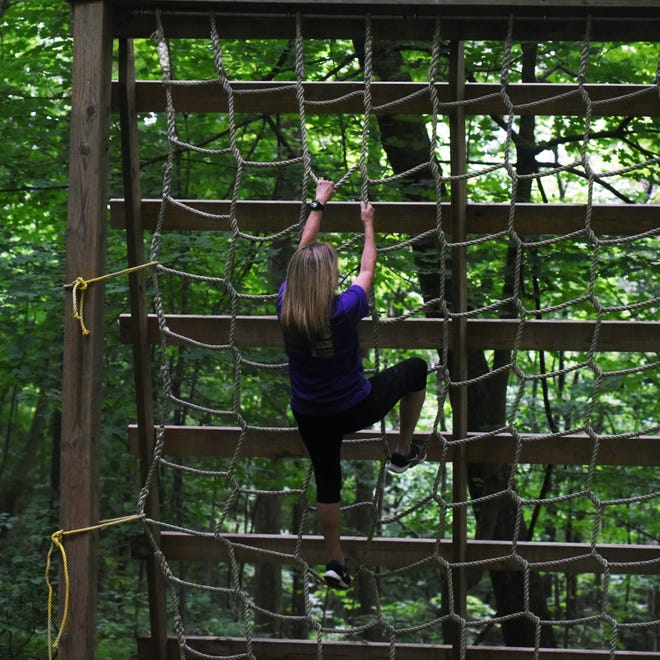 Lisa Emerson, owner of the Nightmare Challenge 5K Mud run course with her husband, Lee, climbs one of the rope ladders on the course. The event is open to individuals and teams and will be held on July 13.