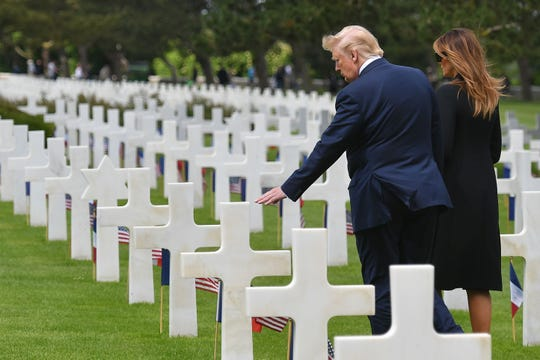 President Donald Trump first lady Melania Trump visit graves after a French-US ceremony at the Normandy American Cemetery and Memorial in Colleville-sur-Mer, Normandy on June 6, 2019.