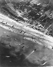 US Army Air Corps photographers making aerial images of D-Day beach traffic, as photographed from a Ninth Air Force bomber showing vehicle lanes leading away from the landing areas, and landing craft left aground by the tide during the Allied Invasion, on the beaches of Normandy.