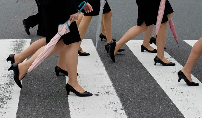 Young women wearing dark suits worn by new employees cross a street in Tokyo.