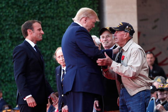U.S. President Donald Trump greets a U.S War veteran as French President Emmanuel Macron, left, looks on, during a ceremony to mark the 75th anniversary of D-Day at the Normandy American Cemetery in Colleville-sur-Mer, Normandy, France, Thursday, June 6, 2019. World leaders are gathered Thursday in France to mark the 75th anniversary of the D-Day landings. (Ian Langsdon/POOL via AP) ORG XMIT: PAR180