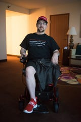 Kevin Roster, in his Las Vegas hotel room, is wearing T-shirts and hats with messages about sarcoma and Compassion & Choices, a nonprofit that advocates for end-of-life options.