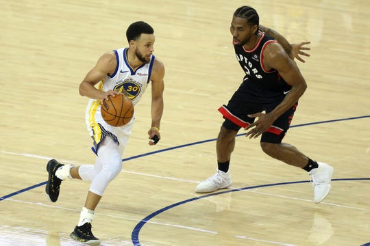 Golden State Warriors guard Stephen Curry (30) moves the ball past Toronto Raptors forward Kawhi Leonard (2) during the third quarter in game three of the 2019 NBA Finals at Oracle Arena.