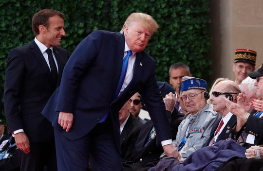 President Donald Trump and French President Emmanuel Macron, left, greet a U.S. veteran during a ceremony to mark the 75th anniversary of D-Day in Normandy.