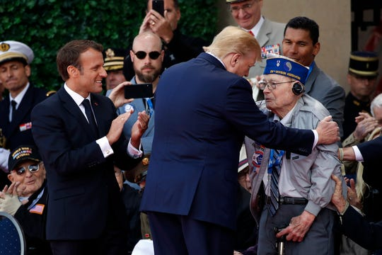 President Donald Trump and French President Emmanuel Macron talk to World War II veterans Thursday during a ceremony to mark the 75th anniversary of D-Day.