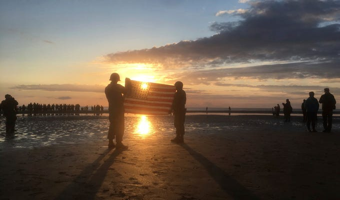 Re-enactors hold an American flag at sunrise as part of events to mark the 75th anniversary of D-Day on Omaha Beach in Vierville-sur-Mer, Normandy, France, June 6, 2019.