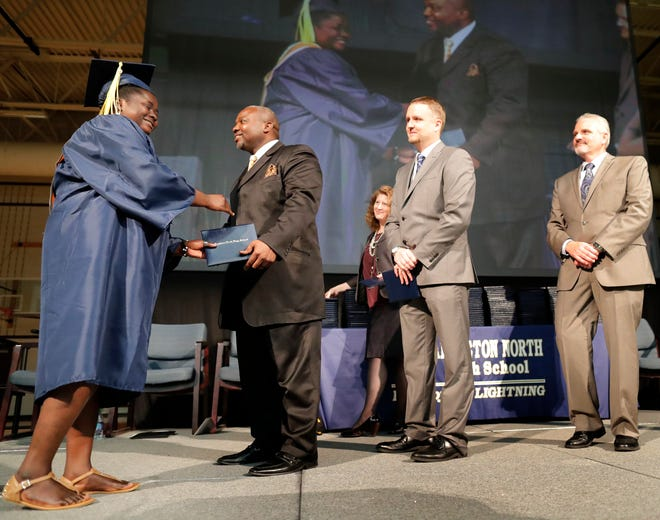 Mardia Adams receives her diploma from the Rev. Alvin Dupree, a member of the Appleton Area School District Board of Education, during the 2019 Appleton North High School commencement ceremony Thursday. Dupree's speech, which was laden with references to Christianity, has sparked controversy in the district and community.