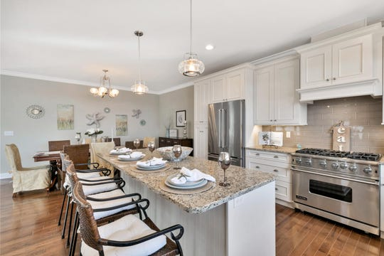The gourmet kitchen offers a breakfast nook with granite stone counter tops and custom cabinetry.
