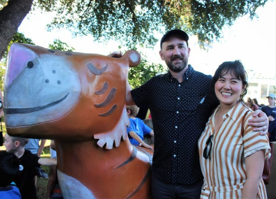 "Author-illustrator Peter Brown poses Thursday with girlfriend Susan Fang at the Mr. Tiger sculpture based on his book, ""Mr. Tiger Goes Wild."" It's the newest sculpture at Adamson-Spalding Storybook Garden in downtown Abilene."
