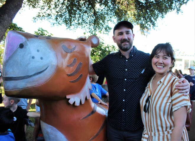 """Author-illustrator Peter Brown poses Thursday with girlfriend Susan Fang at the Mr. Tiger sculpture based on his book, """"Mr. Tiger Goes Wild."""" It's the newest sculpture at Adamson-Spalding Storybook Garden in downtown Abilene."""