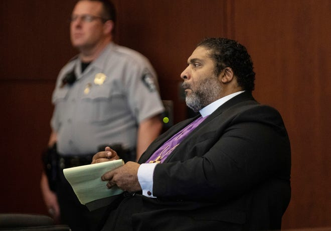 Rev. William Barber II takes notes during pretrial motions Monday, June 3, 2019 at the Wake County Justice Center in Raleigh. Barber and about 30 others were arrested in May of 2017 on charges of second-degree trespassing when they refused to leave the hallways outside state legislators' offices.   (Travis Long/The News & Observer via AP)