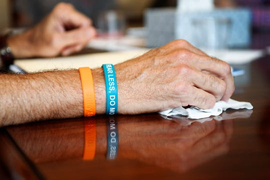"Scott Pritchard, Riley Howell's uncle, holds a tissue while wearing bracelets reading ""Riley Strong"" and ""Fear less, do more"" during an emotional meeting for the Riley Howell Foundation Fund May 31, 2019. Students of Roberson High School, where Howell attended, sold the bracelets as a fundraiser for the foundation."