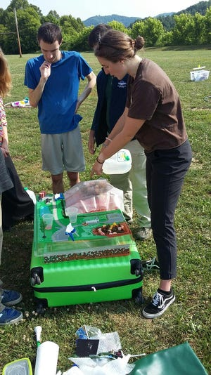 Julia Krebs-Moberg of Asheville Greenworks uses a model to demonstrate how modern landfills help protect groundwater.