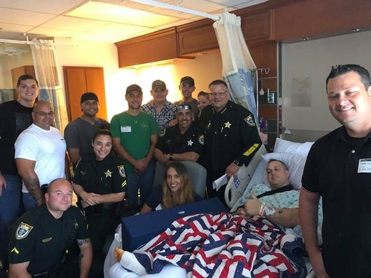 Paul Phillips, 35, gives a thumbs up from his hospital bed while his fellow deputies and friends stand around him on Thursday, June 6, 2016. Sheriff Wayne Ivey said Phillips was a 'great hero' after he was shot several times Tuesday night.
