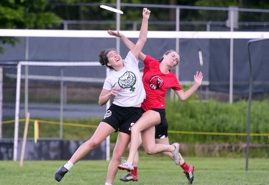 A Montpelier and Champlain Valley player leap to grab the frisbee during Thursday's girls ultimate state championship game in Montpelier.