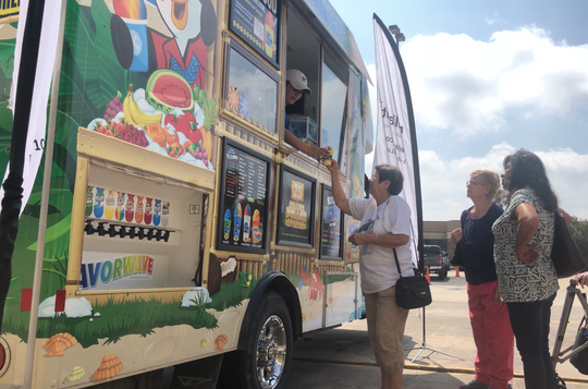 Members of the Greenwood Senior Center receive snow cones to celebrate the opening of the Beat the Heat cooling centers.