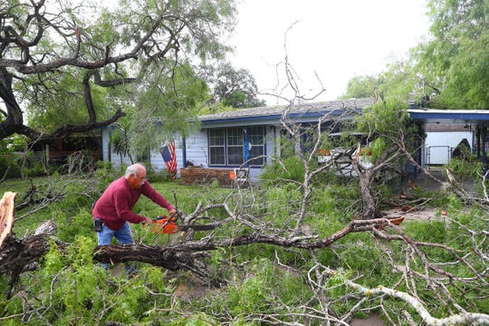 Rudy Rodriguez clears downed trees on West D Avenue in Kingsville on Friday, June 7, 2019, the morning after severe weather.
