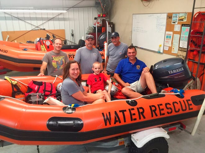 In this photo provided by Oak Island Water Rescue members of the Oak Island Water Rescue pose with the child who was rescued from a unicorn raft, hundreds of yards off the beach in Oak Island, N.C., Wednesday, June 5, 2019. (Carl Mauney/Oak Island Water Rescue via AP)