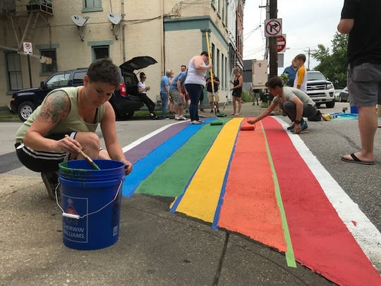 Katie Meyer puts finishing touches on the green stripe in the rainbow crosswalk in Covington on June 7.