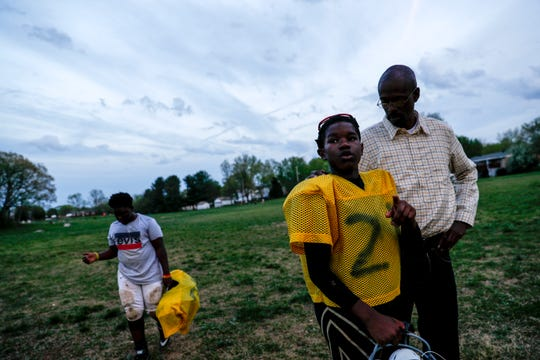 Pooky Bogertey walks off the field with Omari Medlock, 10, to ask about why he can't make a weekend football game at practice for the Clarksville Screaming Eagles youth football team at Bel Aire Park in Clarksville, Tenn., on Thursday, April 11, 2019.