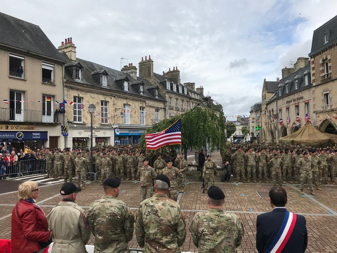 101st Airborne troops held a mass reenlistment ceremony in Carentan, France, on June 7, 2019, recreating a famous photo taken there 75 years ago following the city's liberation.