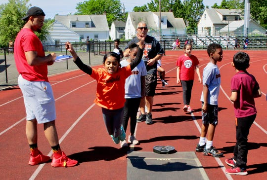 Elementary school students competing in the standing long jump at Linden Public Schools' annual Paul Blue Elementary Track and Field Meet.
