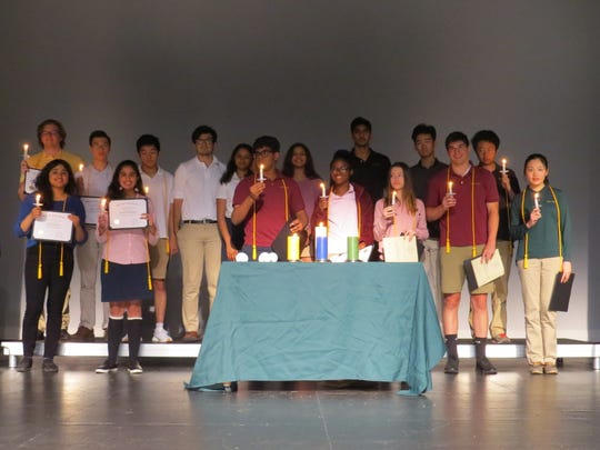The new inductees to the cum laude society participate in the candle ceremony.