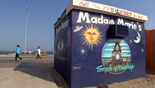 People walk past Madam Marie's Temple of Knowledge on the Asbury Park boardwalk.