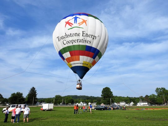 The Touchstone Energy Cooperatives hot air balloon gave tethered rides to visitors at the Coshocton Hot Air Balloon Festival at the Coshocton County Fairgrounds. The balloon would go up about 100 feet for a minute or so with passengers before coming back down.