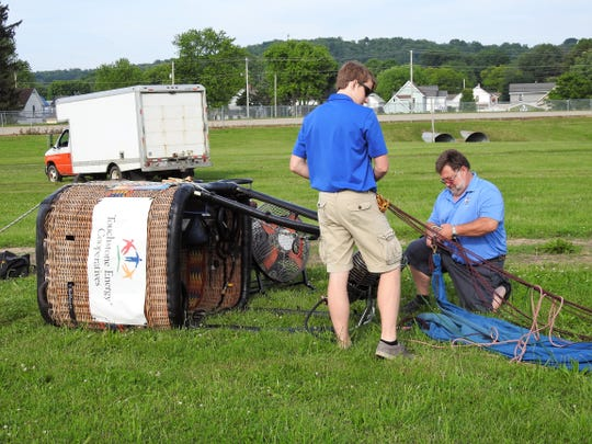Bob Scobee and his son, Scott, prepare the Touchstone Energy Cooperatives hot air balloon Thursday at the Coshocton County Fairgrounds for the Coshocton Hot Air Balloon Festival. This week Scobee is a competitive pilot and giving tethered balloon rides to visitors.