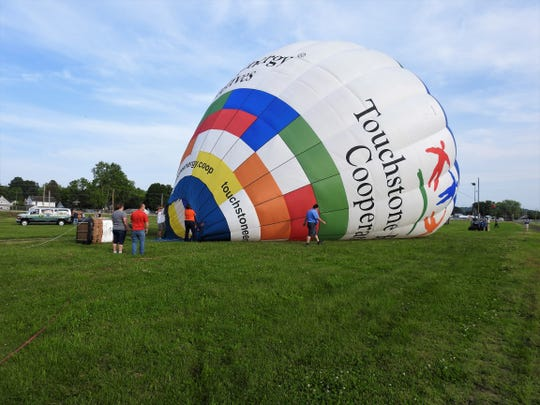 The Touchstone Energy Cooperatives hot air balloon is inflated Thursday at the Coshocton County Fairground prior to giving tethered balloon rides to visitors of the Coshocton Hot Air Balloon Festival.
