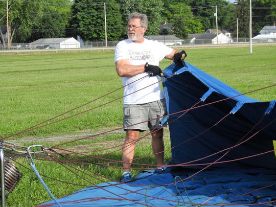 Ken Cramer holds a hot air balloon open for inflation Thursday at the Coshocton Hot Air Balloon Festival at the Coshocton County Fairgrounds. Cramer was a pilot for 22 years and still helps with the festival every year.