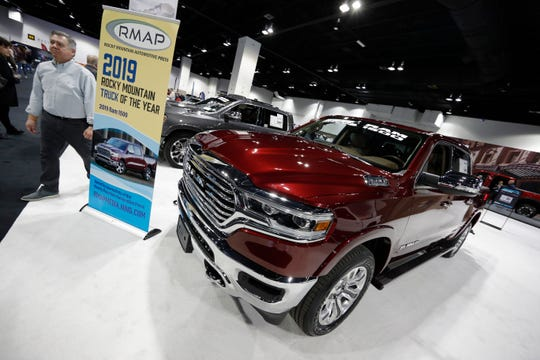 Buyers look over a 2019 Ram pickup truck on display at the auto show in Denver. Fiat Chrysler is recalling nearly 343,000 Ram pickup trucks worldwide because the air bags may not inflate in a crash.