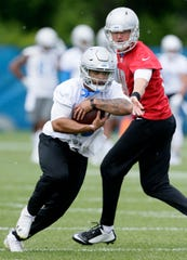 Detroit Lions running back Ty Johnson takes a handoff from quarterback Connor Cook during practice Tuesday, June 4, 2019, in Allen Park.