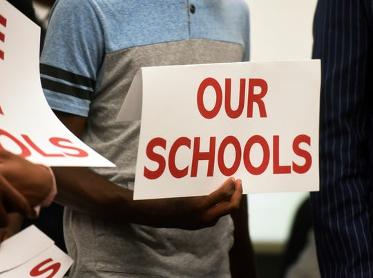 Benton Harbor High School students hold cards during a news conference, Thursday, May 30, 2019, at Benton Harbor City Hall in Benton Harbor, Mich., in response to the state's proposals to close Benton Harbor High School or face a complete shutdown of the district. The state says district finances and academic performance are poor. (Don Campbell/The Herald-Palladium via AP)