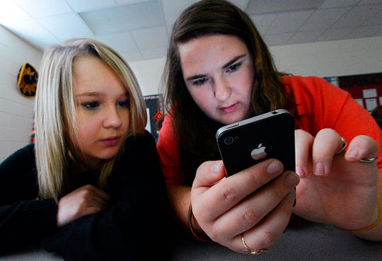 Hartselle High School students Lissa Blagburn and Brantlee Wright use an iPhone as they work on a networked lesson in Spanish class in Hartselle, Ala.