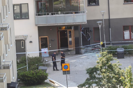 Policemen guard the entrance to a block of flats that were hit by an explosion, in Linkoping, Sweden.
