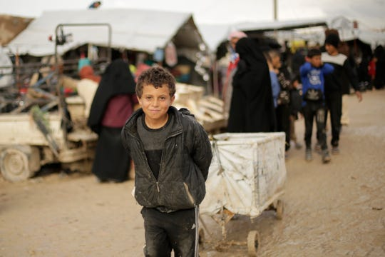 A boy who works as a porter pauses for a portrait in the marketplace at Al-Hol camp, where families from Islamic State-held areas are housed, Hassakeh province, Syria, Sunday, March 31, 2019.