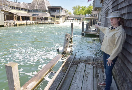 Amanda Holmes, executive director of the Fishtown Preservation Society, stands on a boardwalk Friday in Leland's Fishtown, which is reaching near-record water levels.