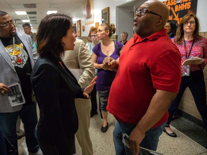 Poppy Sias-Hernandez, regional director of community affairs for Gov. Gretchen Whitmer, talks with local minister Don McAfee at Benton Harbor High School, which the state says must close to salvage the struggling district.