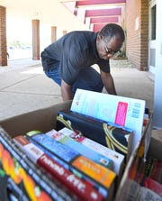 Ryan Reentry Center jail librarian Maurice Duke helps carry in books delivered by Ira Memaj in Detroit, Friday.
