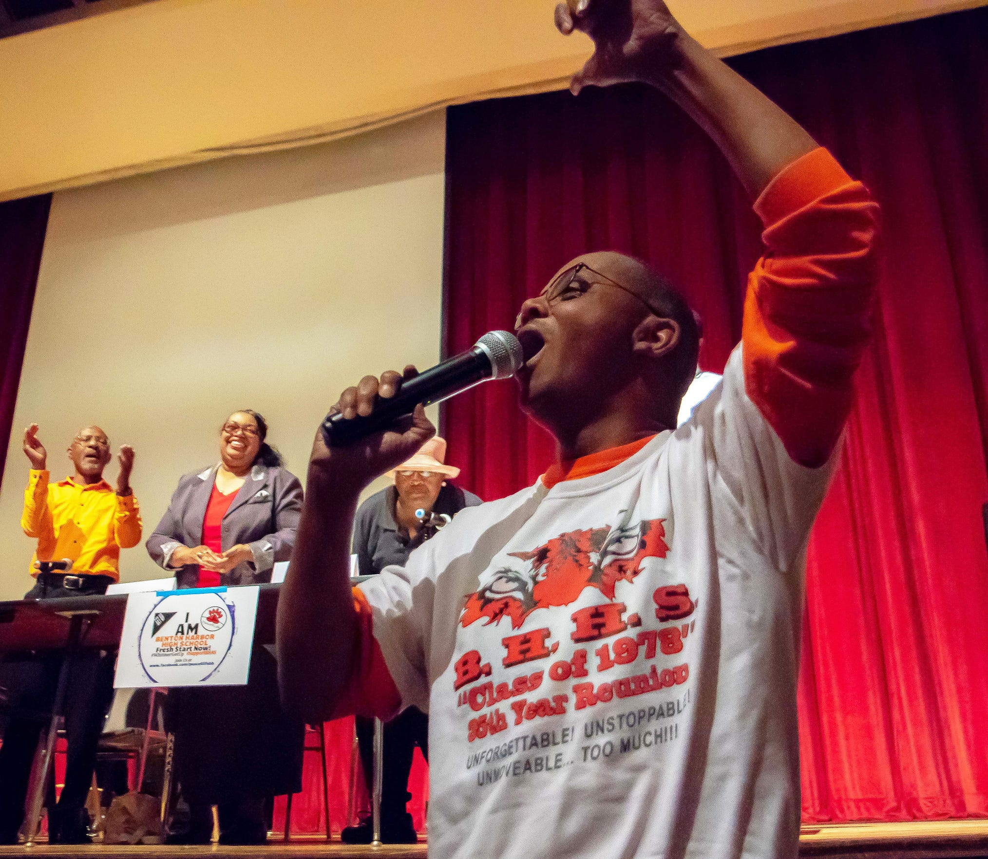 Former Benton Harbor High School principal Rodger Tripplett leads the crowd in the school's fight song at last week's school board meeting.