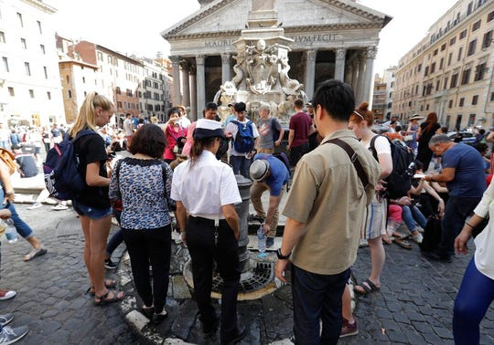 A city police officer watches over as a man refills a bottle with water in front of the Pantheon, in Rome, Friday, June 7, 2019.