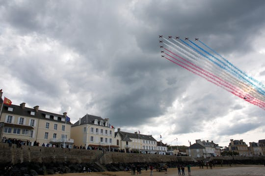 Spectators watch as jets perform a flyover during events to mark the 75th anniversary of D-Day in Arromanches, Normandy, France.